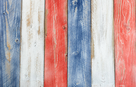 Stressed wooden boards painted red, white and blue for patriotic concept of United States of America. Layout in vertical format. Фото со стока