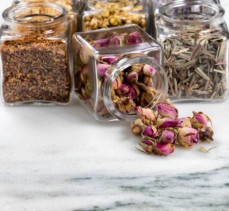 Vooraanzicht van kruiden en specerijen in glazen potten met een pot morsen op witte marmeren steen. Selectieve focus op gemorste rozenknopjes.