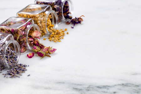 Front view of herbs and spices in glass jars spilling onto white marble stone. Selective focus on second jar with rose buds. Stock Photo