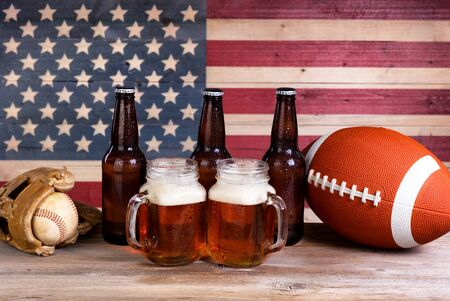 mitt: Two pint jars filled with beer, full bottles, football and baseball mitt with vintage wooden USA flag in background.