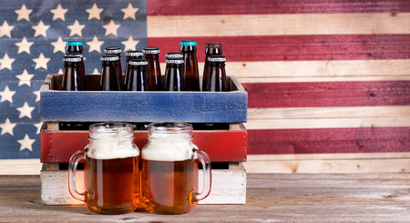 unopen: Two pint jars filled with beer, crate with unopen bottle and vintage wooden USA flag in background. Holiday party concept. Stock Photo