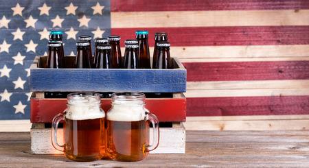 两品脱瓶子装满啤酒,箱子用未打开瓶和葡萄酒木美国旗子在背景中。假日党的概念。