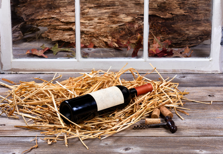 cork screw: Bottle of wine on straw with old cork screw on rustic wood and window in background. Stock Photo