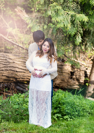 shaped hands: Expecting mom and dad holding each other with heart shaped hands over her abdomen with woods in background. Haze lighting effect on left side of image. Stock Photo