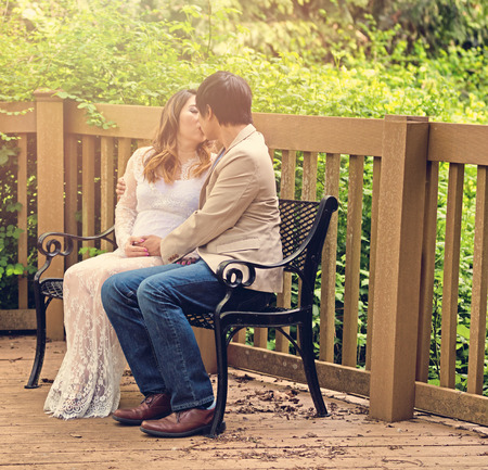Expecting mom and dad kissing on bench patio with woods in background. Haze light effect applied to image.
