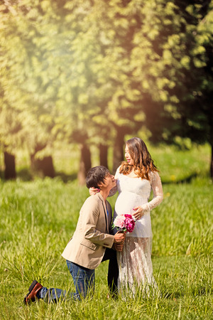 knell: Future dad, with flowers, kneeling to expecting mom in open grassy field. Haze light effect applied to image.