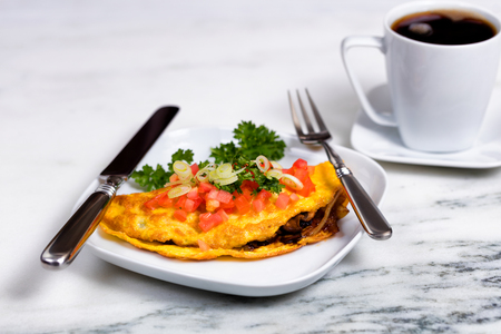 Close up of freshly made omelet with sliced tomato, onion, parsley, and mushroom in dish with silverware on white marble counter. Dark coffee in background.
