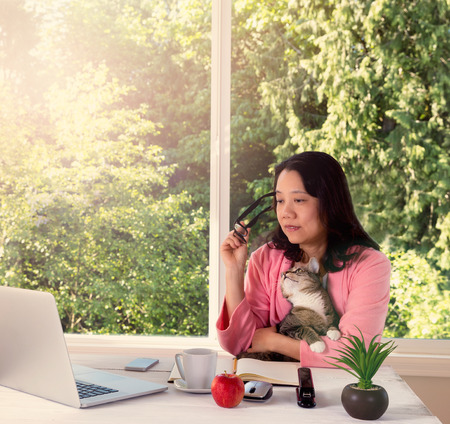 Mature woman, wearing pink bathrobe, holding her family cat while working from home in front of large window with bright daylight and trees in background. Haze light effect applied to image.