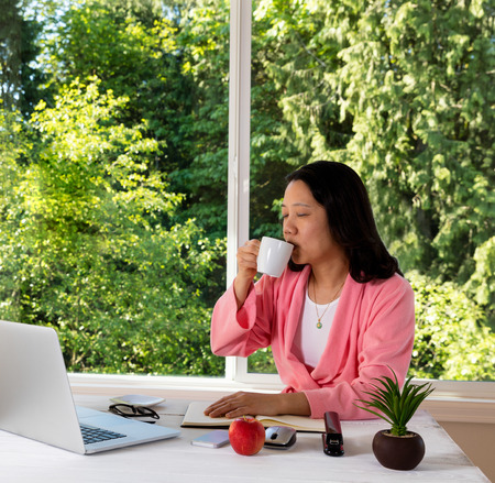 causal: Mature woman, eyes closed, enjoying her morning coffee while working from home in front of large daylight window.