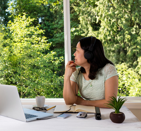 looking out: Mature woman, looking out window while holding apple in hand, working at home