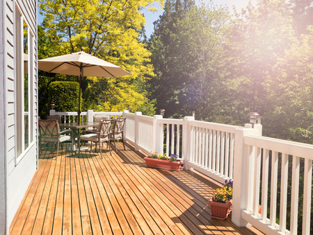 cedar: Afternoon bright daylight on outdoor home cedar deck with furniture and open umbrella. Light effect applied to image. Horizontal layout. Stock Photo