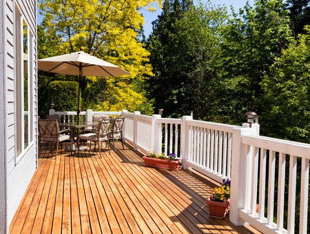 home furniture: Home outdoor cedar deck with furniture and open umbrella during nice bright day. Horizontal layout.