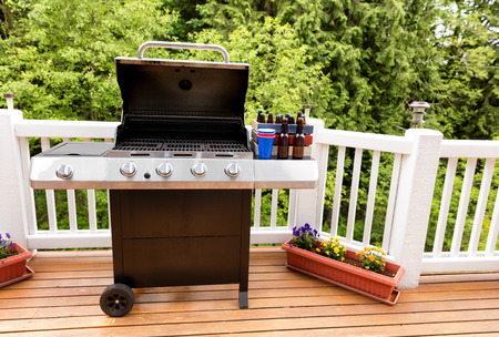 bottled beer: Open large barbecue cooker, bottled beer, cup, and crate on cedar wood deck with trees in background.