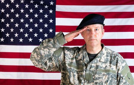 soldato veterano, rivolto in avanti, che saluta con bandiera USA in background.