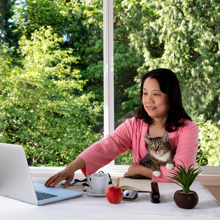 causal: Mature woman, wearing morning attire, holding her family pet cat while working from home in front of large window with bright daylight and trees in background.