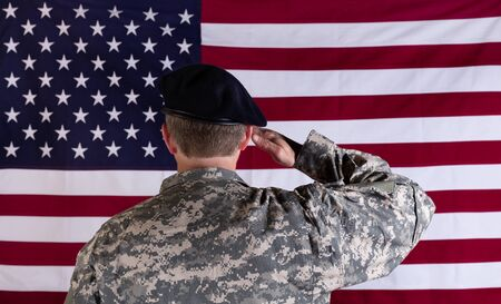 Veteran soldier, back to camera, saluting USA flag.