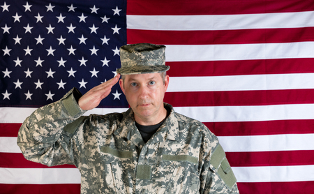 fatigues: Veteran male soldier, facing forward, saluting with USA flag in background.