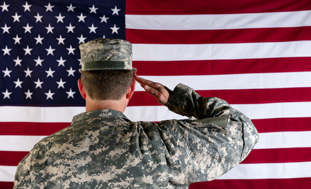 fatigues: Male Veteran soldier, back to camera, saluting United States of America flag.
