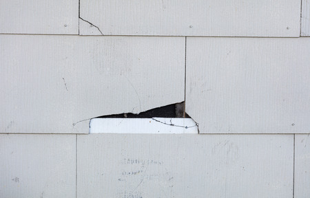 Asbestos siding falling apart due to age. Main focus is on major damage shingle with felt paper underneath.