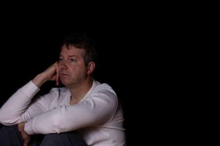 emotionless: Side view of depressed mature man in thought.  Dark background with copy space available.