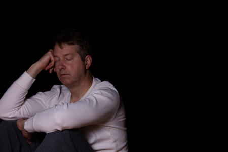 Side view of depressed mature man with eyes closed in thought.  Dark background with copy space available.