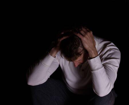persona deprimida: hombre maduro deprimida sosteniendo la cabeza mientras mira hacia abajo. fondo oscuro. Foto de archivo