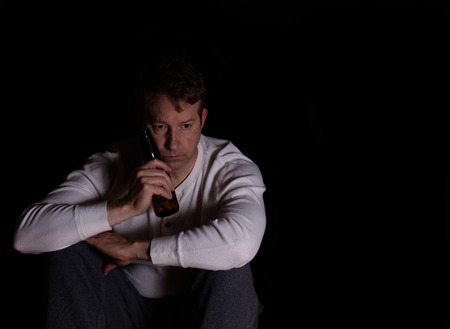 emotionless: Depressed man holding bottle of beer against face while in thought. Dark background.