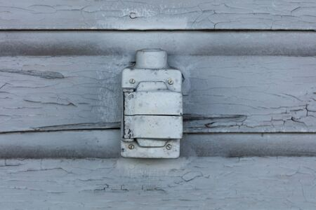 paint box: Old electric outlet box with cracking and peeling lead paint off of wood sliding. Stock Photo