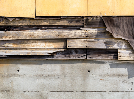 Asbestos siding falling apart with exposed wood and felt underneath. Stock Photo