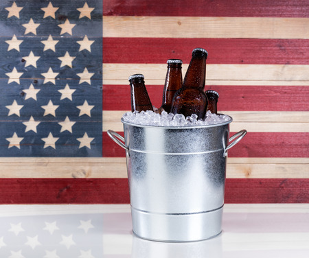 bottled beer: A bucket of cold bottled beer on ice with USA wooden flag in background. Stock Photo
