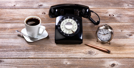 office tool: Vintage desktop with antique telephone, pen, clock and coffee on rustic wooden boards. Stock Photo