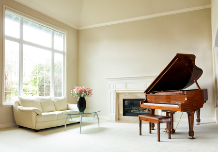 Living room with grand piano, fireplace, sofa and large window with bright daylight coming through.