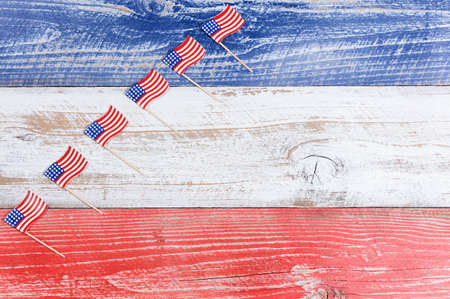 red america: Small USA flags stacked in rising formation on red, white and blue rustic boards. Fourth of July holiday concept for United States of America.
