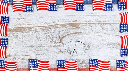 red america: Small USA flags forming complete border on red, white and blue rustic boards. Fourth of July holiday concept for United States of America. Stock Photo