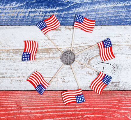 red america: Small USA flags forming circle around American liberty dollar coin on red, white and blue rustic boards. Fourth of July holiday concept for United States of America.