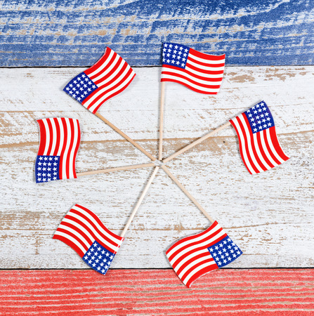 red america: Small USA flags forming pinwheel formation on red, white and blue rustic boards. Fourth of July holiday concept for United States of America. Stock Photo
