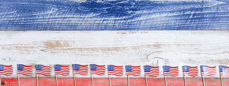 memorial: Small USA flags on bottom of red, white and blue rustic boards. Fourth of July holiday concept for United States of America.