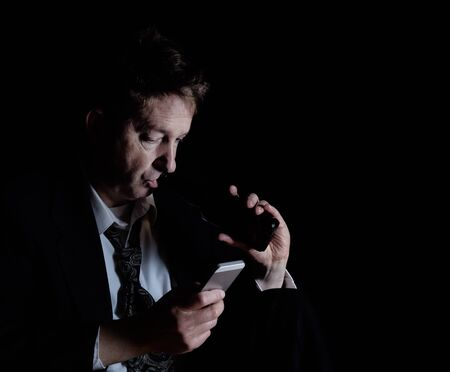 frustrate: Stressed business man on cell phone while drinking a beer.  Dark background with light on subject.