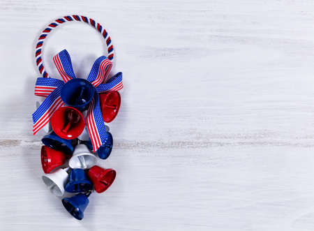 liberty bell: Colorful bells and ribbons on rustic white wooden boards. Fourth of July holiday concept for United States of America.