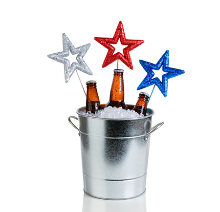 bottled beer: Colorful stars in bucket of ice with bottled beer. Isolated on white with reflection. Fourth of July holiday concept for United States of America.