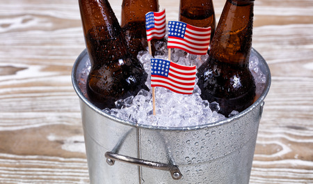 bottled beer: Miniature USA flags in bucket of ice with bottled beer. Fourth of July holiday concept for United States of America.