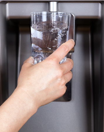 refrigerator: Hand holding drinking glass while being filled with filtered water from refrigerator