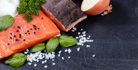 king salmon: Organic wild king salmon fillet with fresh herbs, spices and vegetables on black stone board. Healthy cooking concept.