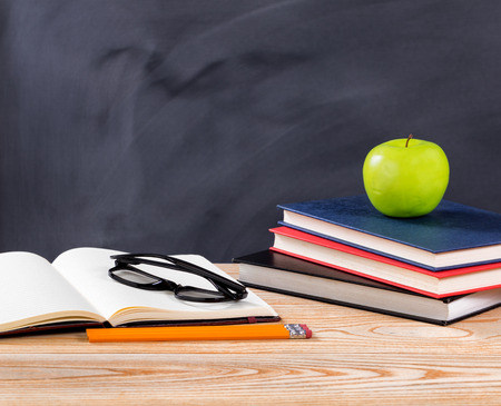 erased: Back to school concept with reading glasses, pencils, notepad, books and green apple on desktop with erased black chalkboard in background. Stock Photo