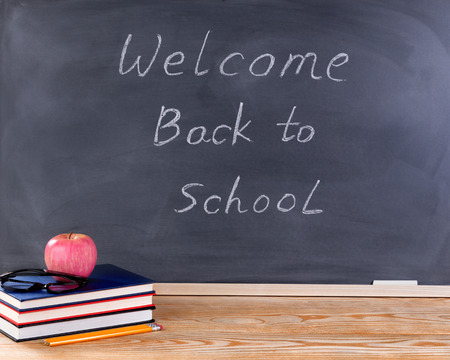 erased: Back to school concept with welcome back to school message on erased black chalkboard plus desktop and supplies.