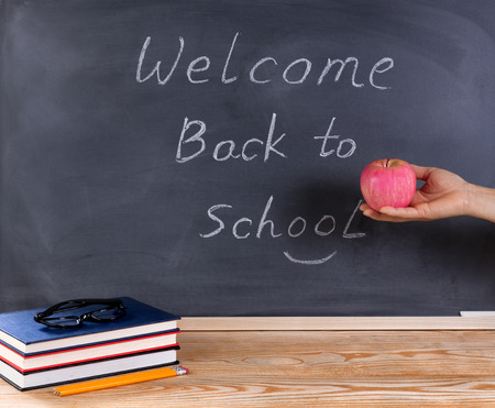 erased: Teacher hand holding red apple with erased black chalkboard and desktop in image. Back to school concept.