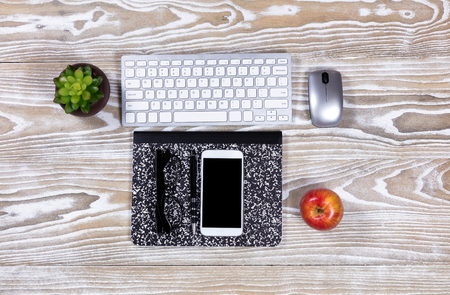 supple: Old desktop with notepad, pen, apple, computer keyboard, plant, mouse, reading glasses, apple and cell phone. Overhead view of display. Stock Photo