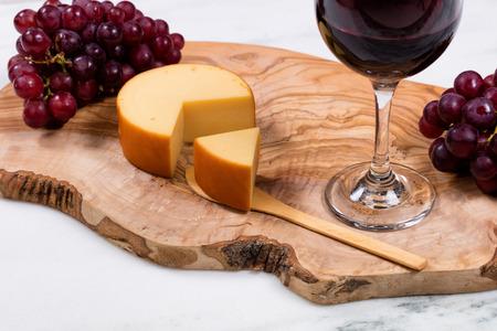 kulinarne: Bliska plasterki sera smakoszy z czerwonego wina i winogron na drewnianym serwera w tle. Selektywne fokus na przedniej sera klina. Zdjęcie Seryjne