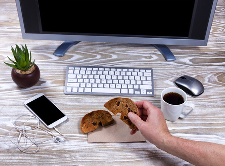 snack: Overhead view of hand holding part of bagel on office desktop. Stock Photo