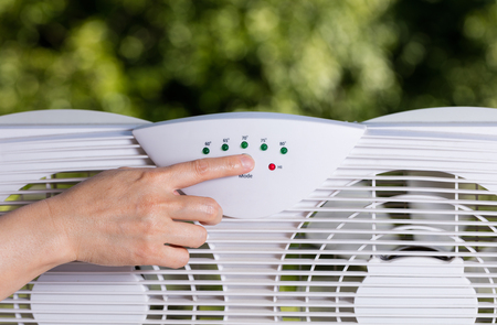 two way: Hand selection temperature on two way window fan in home window with blurred out trees in background.